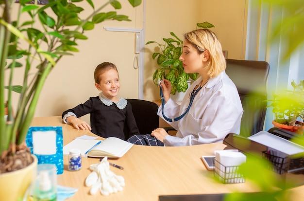 Kinderarts arts die een kind onderzoekt in een comfortabel medisch kantoor