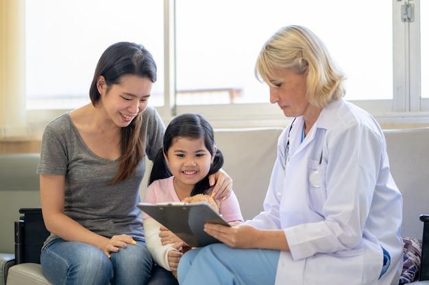 Kinderarts arts die een klein aziatisch meisje onderzoekt met een gebroken arm die een gipsverband draagt in het ziekenhuis