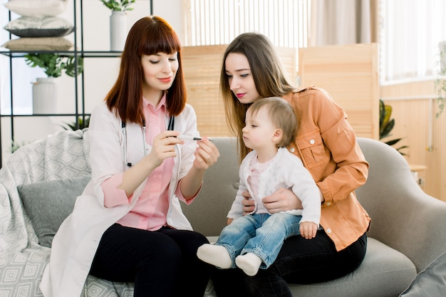 Kinderarts arts die temperatuur van weinig babymeisje in de wapens van moeder onderzoekt. de arts die van kinderen de temperatuur van de baby in het ziekenhuis controleert