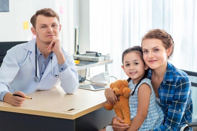 Kinderarts (arts) man, moeder en dochtertje lachend in het ziekenhuis.