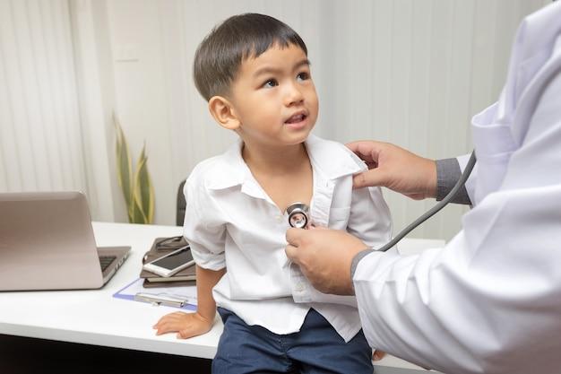 Kinderarts diagnosticeert een kleine patiënt met behulp van een stethoscoop