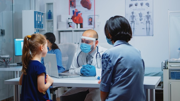 Kinderarts die de behandeling uitlegt aan een klein meisje dat een beschermingsmasker draagt. specialist in geneeskunde met beschermingsmasker die gezondheidsdiensten, consultatie, behandeling in het ziekenhuis biedt tijdens covid-19