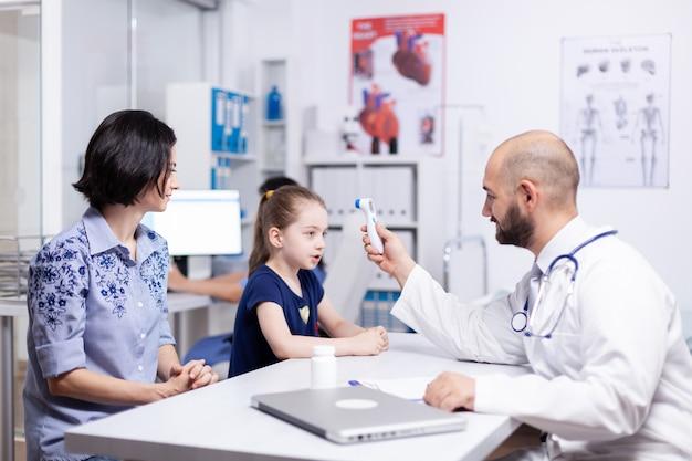 Kinderarts die de temperatuur van het kind controleert met behulp van een digitale thermometer in een medisch kantoor. medisch specialist in de geneeskunde die medische zorg onderzoekt.