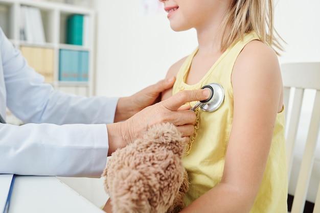 Kinderarts hartslag van meisje controleren