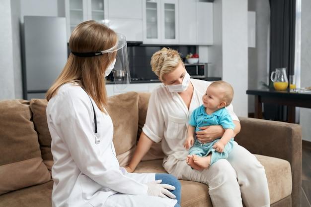 Kinderarts in medisch masker bezoekende baby thuis
