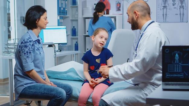 Kinderarts luistert kind symptomen die gezondheidsproblemen proberen te behandelen. gezondheidszorgbeoefenaar, arts, specialist in de geneeskunde die zorg verleent consultatie diagnostische behandeling in het ziekenhuis.
