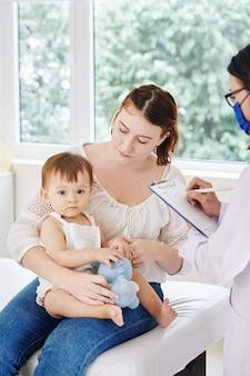 Kinderarts luistert naar klachten van jonge moeder en maakt aantekeningen op medische kaart