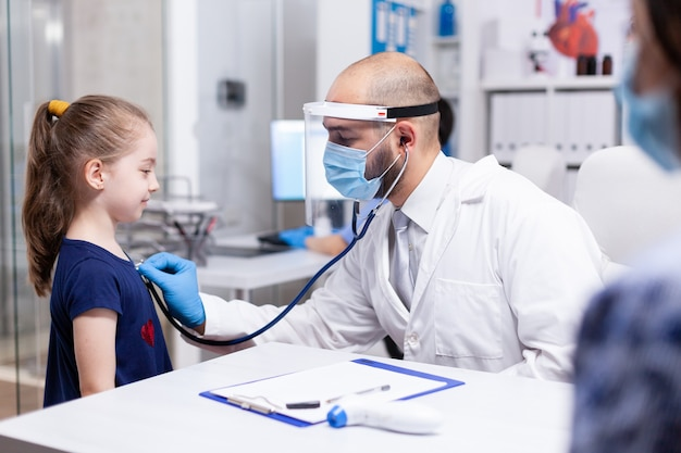 Kinderarts met gezichtsmasker tegen coronavirus luisterend kinderhart met stethoscoop tijdens consult. arts-specialist die consultaties in de gezondheidszorg verleent.