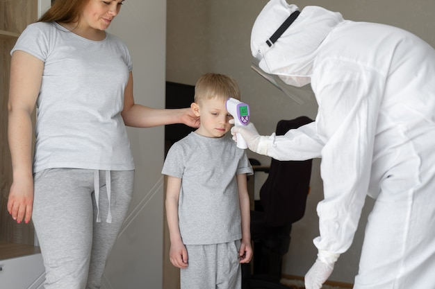 Kinderarts of arts controleert de lichaamstemperatuur van de jongens in de elementaire leeftijd