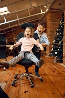 Kinderbloggers die een grapje maken voor de camera, kerstblog, kleine vloggers. kinderen bloggen in de thuisstudio, sociale media voor jong publiek, online internetuitzending