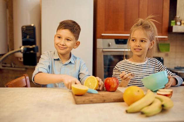 Kinderbloggers maken eetvlogs, kleine vloggers. kinderen bloggen in de thuisstudio, sociale media voor jong publiek, online internetuitzending