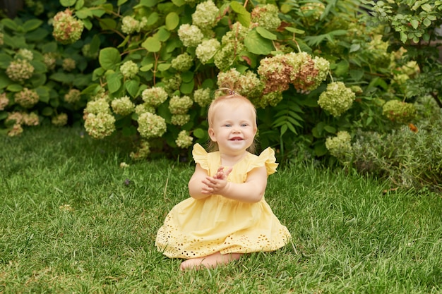 Kinderdag, kindmeisje op groen gras in de zomer