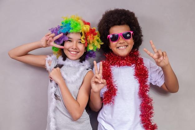 Kinderdagconcept. twee kinderen, een afrojongen en een aziatisch meisje in kleurrijke kleren die feesten