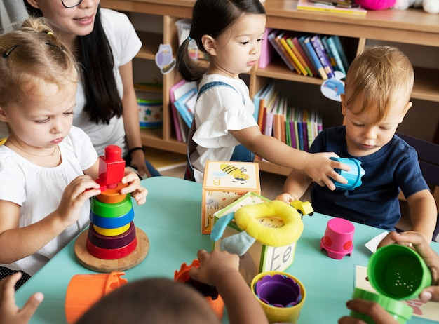 Kinderdagverblijfkinderen die met leraar in het klaslokaal spelen