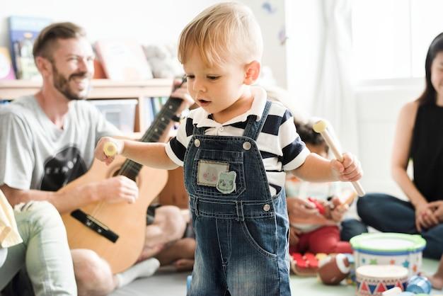 Kinderdagverblijfkinderen die met muzikale instrumenten in het klaslokaal spelen