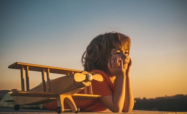 Kinderdromen en verbeeldingsconcept dromend kind dat met speelgoed houten vliegtuig speelt tegen de zomer ...