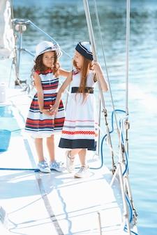 Kinderen aan boord van een zeiljacht. tiener of kind meisjes buiten.