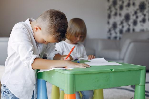 Kinderen aan de groene tafel en tekenen