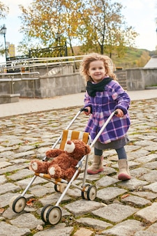 Kinderen baby in retro herfst lente kleding. klein kind zitten lachend in de natuur, sjaal om zijn nek, koel weer.