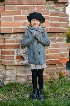 Kinderen baby in retro herfst lente kleding. kleine kindzitting die in aard glimlacht