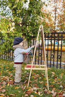 Kinderen baby in retro herfst lente kleding. kleine kindzitting die in aard, sjaal glimlacht
