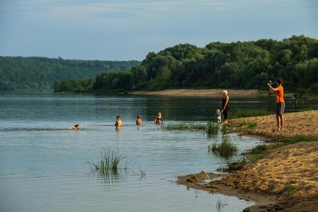 Kinderen baden en vissen op de oever van de rivier.
