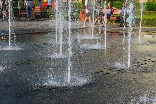 Kinderen baden in de fontein op een warme zomerdag.