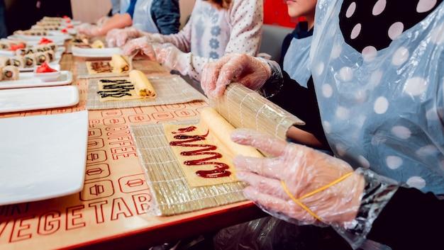 Kinderen bereiden sushi en broodjes. masterclass restaurant.