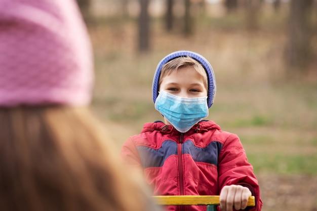 Kinderen beschermen zichzelf met medische maskers terwijl ze buiten spelen. gevaarlijk buiten spelen terwijl coronavirus in quarantaine staat