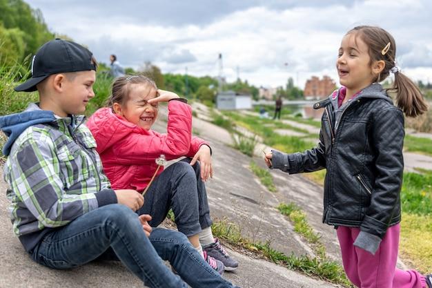 Kinderen bespreken iets terwijl ze in de natuur zitten met paardebloemen in hun handen.