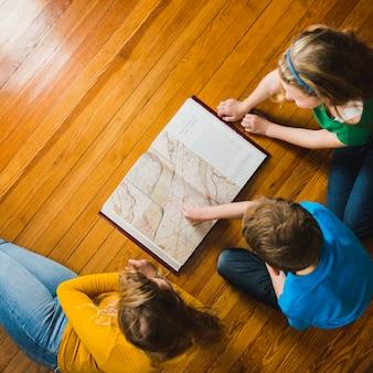 Kinderen bestuderen boekillustraties op verdieping