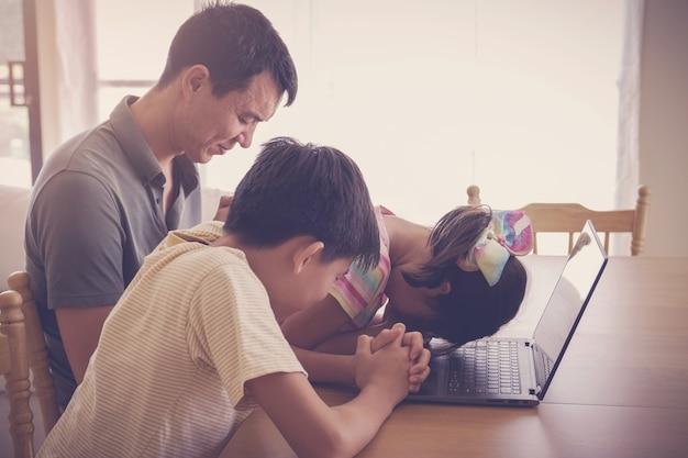 Kinderen bidden samen met vader / ouder met laptop, familie en kinderen aanbidden thuis samen online