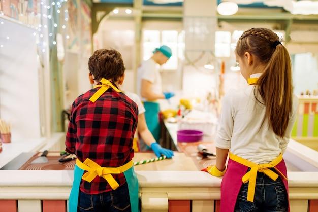 Kinderen bij patisserie leren karamel maken