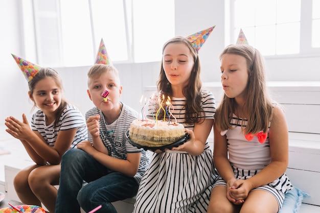 Kinderen blaast verjaardagskaarsen uit en plezier hebben