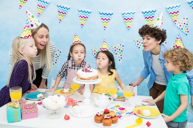 Kinderen blazen kaarsen op verjaardagsfeestje