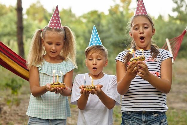 Kinderen blazen kaarsjes op verjaardagstaart. kinderfeestdecoratie en eten. jongen en meisjes vieren verjaardag in de tuin met hangmat. kinderen met snoep.