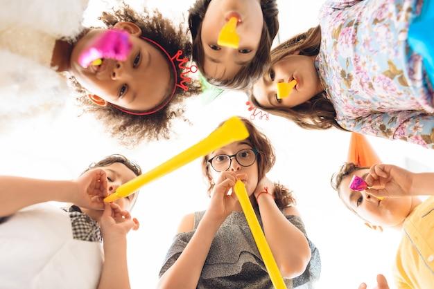 Kinderen blazen op feestelijke pijpen op verjaardagsfeestje