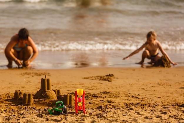 Kinderen bouwen een zandkasteel op het strand