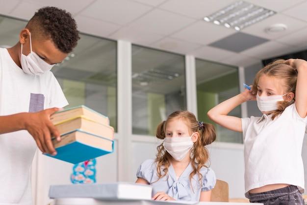 Kinderen brengen samen tijd door in de klas tijdens pandemische tijd