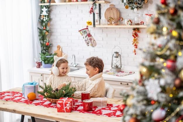 Kinderen broer en zus in de keuken wachten op kerstmis. gelukkige kinderen aan de keukentafel die cadeautjes opent