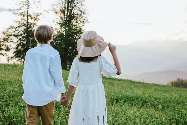 Kinderen broer en zus vrienden van achteren buiten bij zonsondergang, landelijke scène, eerste liefde