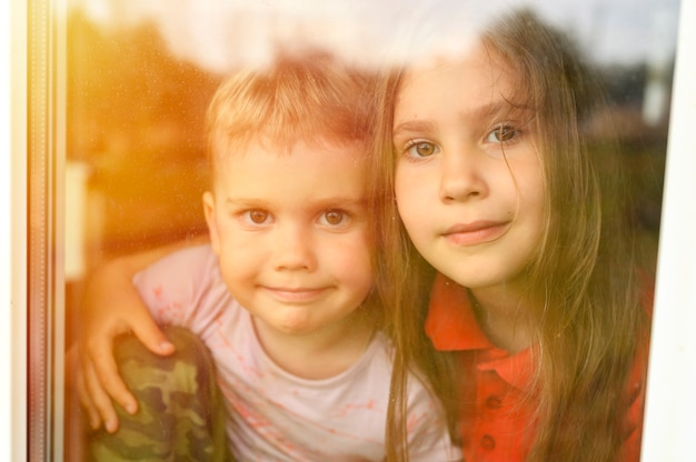 Kinderen broers en zussen jongen en meisje kijkt door het raam tijdens covid-19 quarantaine. blijf thuis, laten we allemaal goed zijn. gloed