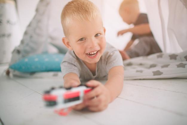 Kinderen broers liggen op de vloer. jongens spelen 's ochtends thuis met speelgoedauto's. casual levensstijl in de slaapkamer.