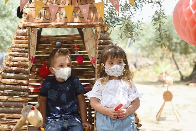 Kinderen buiten spelen in een houten huis met een masker