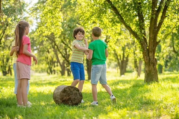 Kinderen, communicatie. jongens en meisjes van junior in korte broeken en felle t-shirts die op een mooie zomerdag op groen gazon kletsen