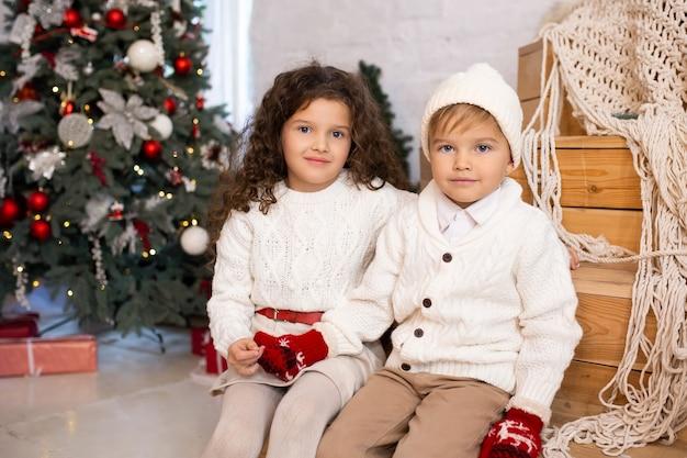 Kinderen dichtbij kerstboom en lichten