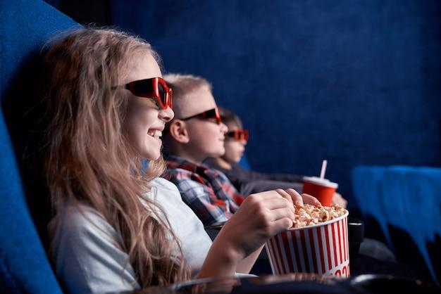 Kinderen die 3d glazen dragen die op grappige film in bioskoop letten