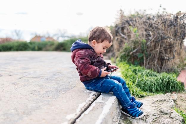 Kinderen die buiten op internet surfen op een mobiele telefoon
