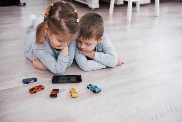 Kinderen die digitale gadgets thuis gebruiken. broer en zus op pyjama kijken naar tekenfilms en spelen games op hun technologietablet