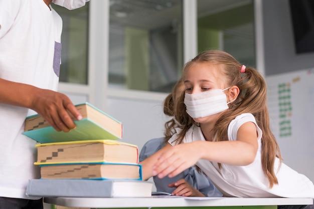 Kinderen die een boek van een bureau willen pakken